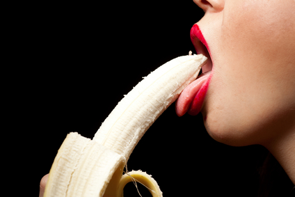 Young woman eating banana