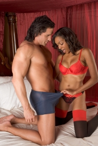 Sensual woman in lingerie looking into panties of Caucasian man